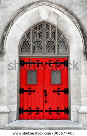 Selective Color closeup of an old set of red double doors in an ornate inset doorway of a downtown building - stock photo