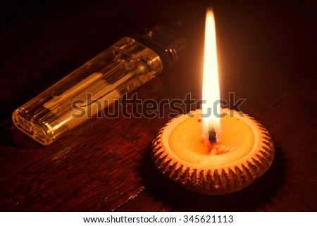 selective focus candle with  lighter on wood background by dark tone. - stock photo