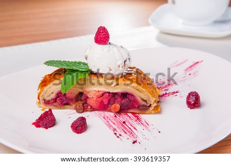 Selective focus Close up Dessert -Berry Strudel with scoop of ice cream, decorated with raspberries and mint leaf  on the white plate on the served table with cup of coffee - stock photo