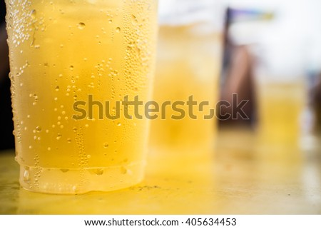 Selective focus Closeup of a frothy glass of golden ale or beer with drop running down the outside of the glass, cropped view image - stock photo