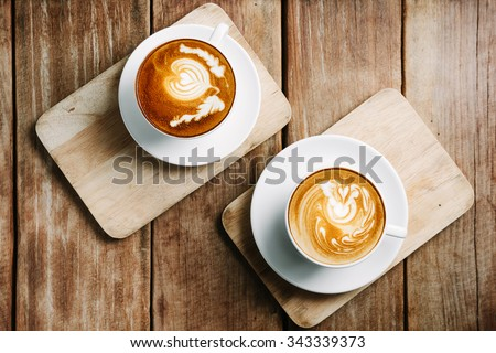 Selective focus cup of hot latte art coffee on wooden table,focus at white foam - stock photo
