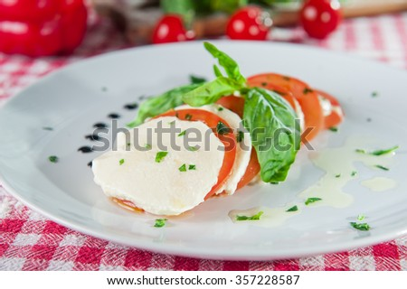 Selective focus delisious italian salad Caprese with Mozzarella cheese and sliced tomatoes decorated with fresh basil on the white round plate on the restaurant table with different ingredients - stock photo