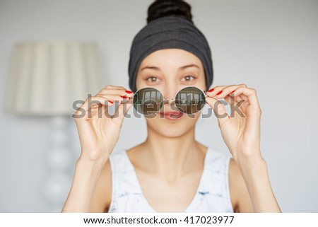Selective focus, film effect. Headshot of young fashionable woman taking off her trendy hipster round sunglasses while looking and smiling at the camera posing isolated against home interior - stock photo