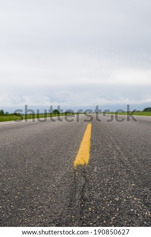 Selective focus foreground portion of the long straight road in Alberta. - stock photo
