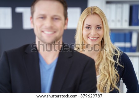 Selective focus front view of smiling blond business woman behind cheerful male co-worker in office - stock photo