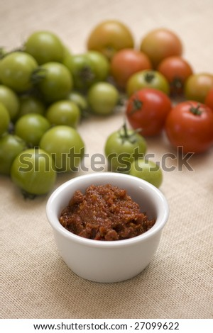 Selective focus image of tomato relish with green and red tomato relish in background. - stock photo