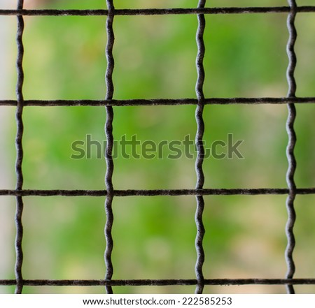 Selective focus is on the fence in the foreground. Also, it is an empty lot behind the metal fence. - stock photo