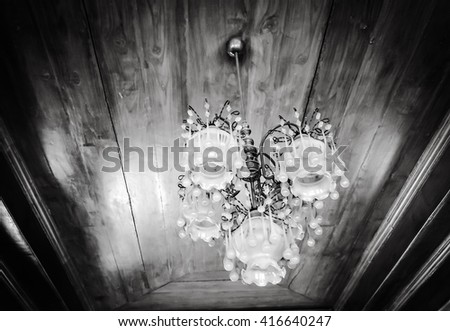 selective focus of Crystal Chandelier , Chandelier ceiling lights on wooden background, black and white tone - stock photo