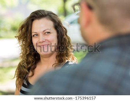 Selective focus of female university student looking at male friend on campus - stock photo