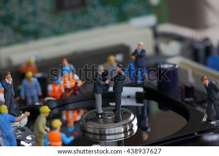 Selective focus of miniature businessman handshake and worker commitment to fixed problem harddisk (hard disk) of Personal computer (PC) as commitment, business and industrial concept. - stock photo