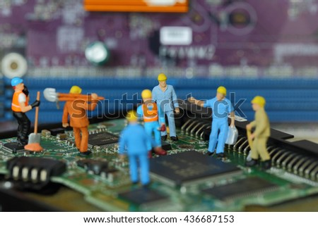 Selective focus of miniature engineer and worker fixed problem or repair on chips and computer mainboard as business and industrial concept. - stock photo