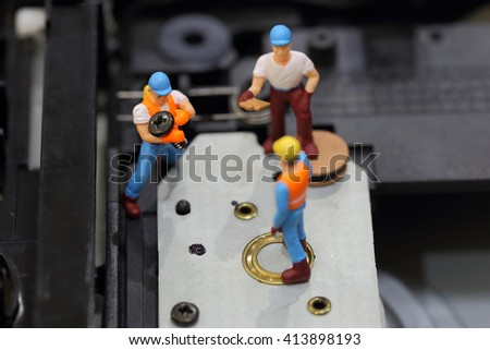 Selective focus of miniature engineer and worker fixed to hold screw for repair cd rom of computer and use for business background. - stock photo