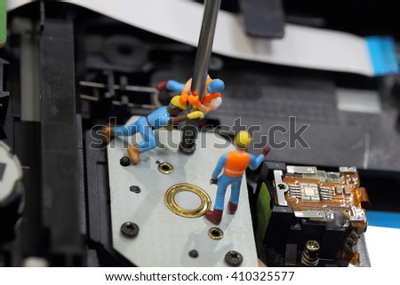 Selective focus of miniature engineer and worker fixed to remove screw by screwdriver for repair cd rom of computer and use for business background. - stock photo