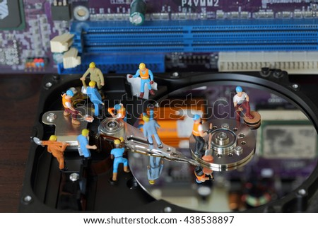 Selective focus of miniature engineer and worker maintenance hard disk and fixed problem hard disk of Personal computer (PC) on blurred mainboard background as industrial concept. - stock photo