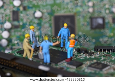 Selective focus of miniature engineer and worker meeting to fixed problem chipset of Personal computer (PC) on blurred mainboard background as business and industrial concept. - stock photo