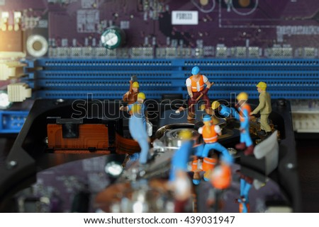 Selective focus of miniature engineer and worker repair hard disk and fixed problem hard disk of Personal computer (PC) on blurred mainboard background as business and industrial concept. - stock photo