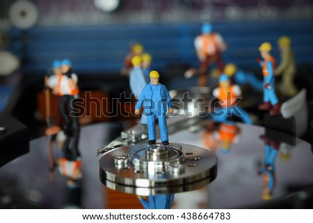 Selective focus of miniature engineer Headman control to fixed problem hard disk of Personal computer (PC) on blurred mainboard background as business and industrial concept. - stock photo