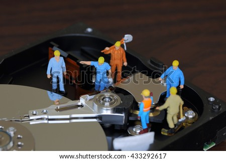 Selective focus of miniature engineer meeting and worker for maintenance hard disk or fixed problem hard disk of Personal computer (PC) as business and industrial concept. - stock photo