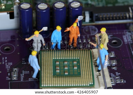 Selective focus of miniature engineer worker to fixed mainboard and repair Control Processing Unit (CPU) processor,  mainboard computer and use for industry background or business background. - stock photo