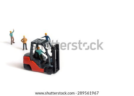 selective focus of miniature worker driving forklift machine, isolated on white. - stock photo