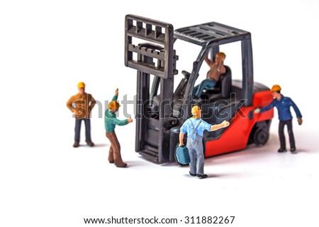 selective focus of miniature worker holding bag and standing front of forklift machine, on white background. - stock photo