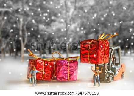 selective focus of miniature worker passenger gift box by forklift machine over winter  forest background,abstract background for new year concept. - stock photo