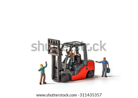 selective focus of miniature worker standing front of forklift machine, on white background.  - stock photo