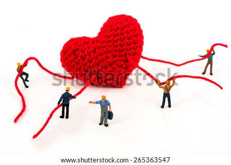 selective focus of miniature workers holding robe of heart on white background , abstract back ground to solution for Heart health and prevent the occurrence of heart disease. - stock photo