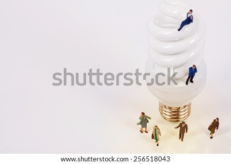 selective focus of miniatures sliding on top of light bulb, abstract background to brain storm idea.  - stock photo