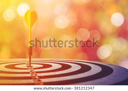 selective focus of old dart target with arrows over bokeh background ,abstract background to target concept. - stock photo