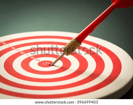 Selective focus of red dart arrow hitting target center of dartboard on black background. Bullseye and Dart. Success/fail business concept. Success hitting target aim goal achievement concept. - stock photo