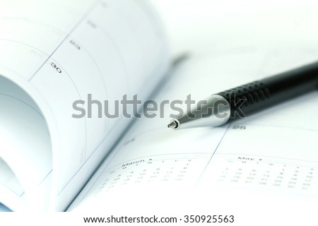 selective focus of the ball pen on opened lined diary book with calendar page - stock photo