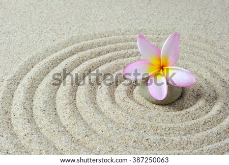 Selective focus of zen stones with frangipani flower with sand background - stock photo