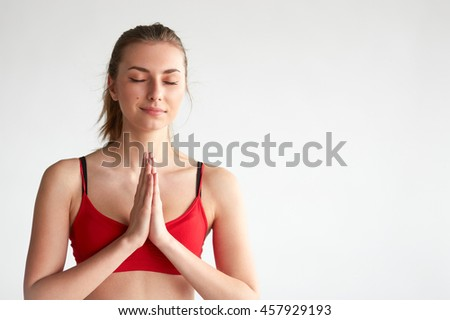 Selective focus on face. Young woman with eyes closed meditating over white background and doing yoga - stock photo