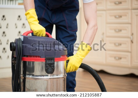Selective focus on janitor wearing white T-shirt blue overalls and yellow rubber gloves turning off the vacuum cleaner. His working place on background - stock photo