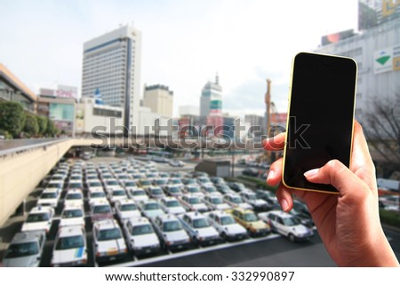 selective focus on mobile phone to take picture of a group of taxi car in the tokyo  - stock photo
