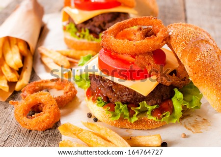 Selective focus on the beef burger and onion rings - stock photo