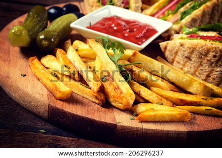 Selective focus on the front french fries on wooden board - stock photo