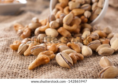 Selective focus on the front pistachio and cashew nut - stock photo