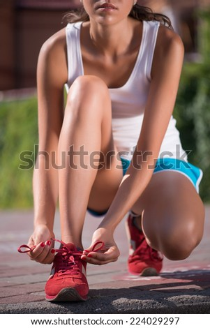Selective focus on the lovely young woman wearing white T-shirt blue shorts and red jogging shoes sitting on the stairs binding her shoelaces - stock photo