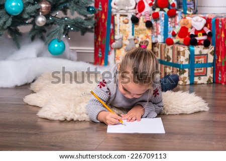 Selective focus on the pretty little fair-haired girl wearing warm sweater and jeans lying on the floor near the Christmas tree writing very diligently something - stock photo