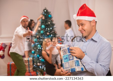 Selective focus on the sly smiling guy wearing red cap of Santa Claus standing alone unpacking the present. His friends near the Christmas tree on background - stock photo