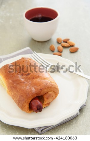Selective focus on the tip of sausage baked in bread beside a cup of coffee that look delicious on the table. - stock photo