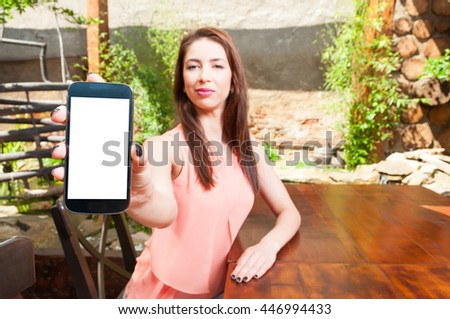 Selective focus on young  woman presenting a withe blank smartphone screen sitting on an outdoor terrace - stock photo