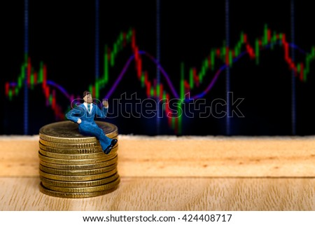selective focus photo of miniature business man in blue suit sitting on 50 cent euro coins over stock chart background, abstract background to money and saving concept. - stock photo