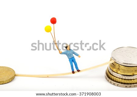 selective focus photo of miniature happy man holding balloon in his hand standing on euro coins on white background, abstract background to money and saving concept. - stock photo