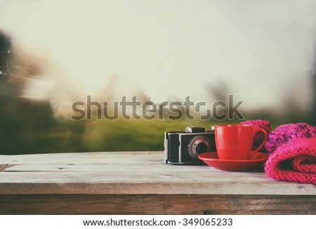 selective focus photo of pink cozy knitted hat with to cup of coffee next to old photo camera on a wooden table. faded style retro filtered and toned  - stock photo