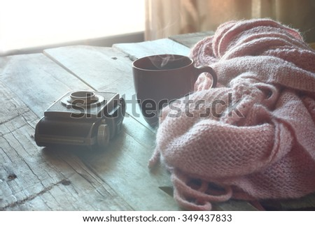 selective focus photo of pink cozy knitted scarf with to cup of coffee next to old photo camera on a wooden table. faded style retro filtered  - stock photo