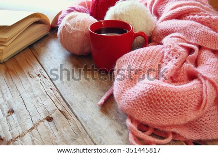 selective focus photo of pink cozy knitted scarf with to cup of coffee, wool yarn balls  and open book on a wooden table  - stock photo