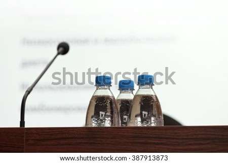 Selective focus photo of three bottles of water on table with blurred screen, microphone and chairs on background in conference room, horizontal view - stock photo